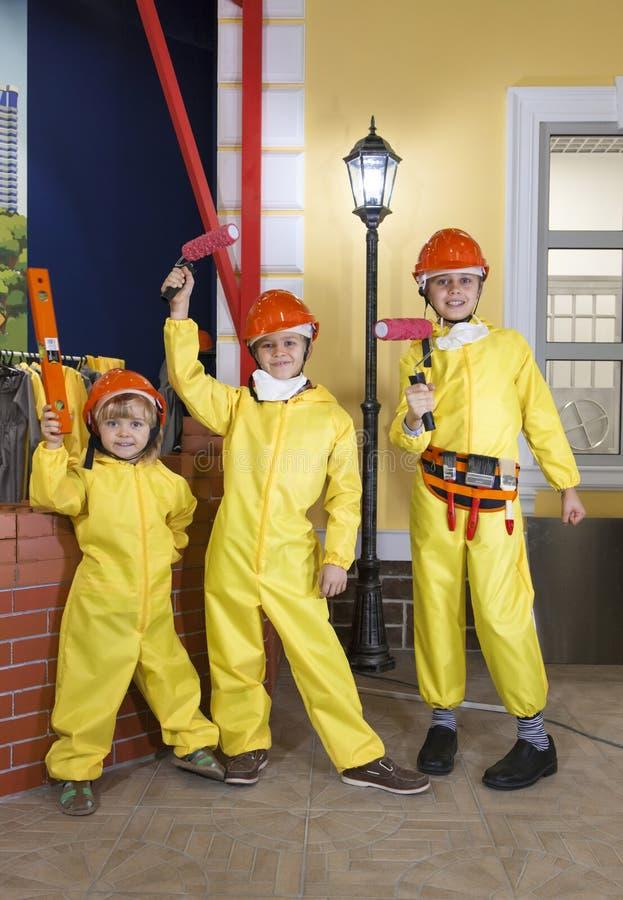 Drei Kinder, die wie die Arbeitskräfte stehen mit Bauwerkzeugen tragen lizenzfreie stockfotografie