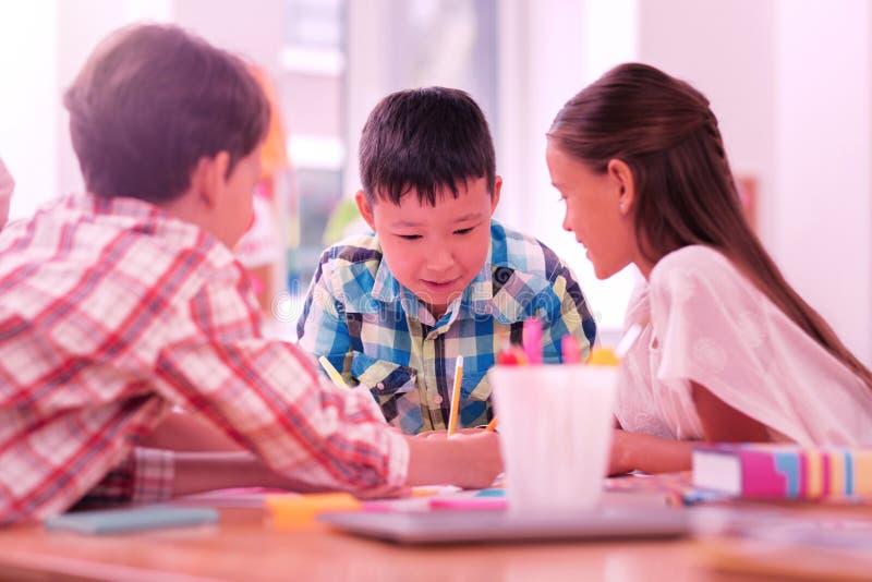 Drei Kinder, die zusammen ein Schulprojekt zeichnen stockbild