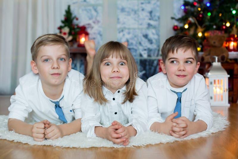 Drei Kinder, Geschwister, ihr Weihnachtsporträt habend lizenzfreies stockfoto