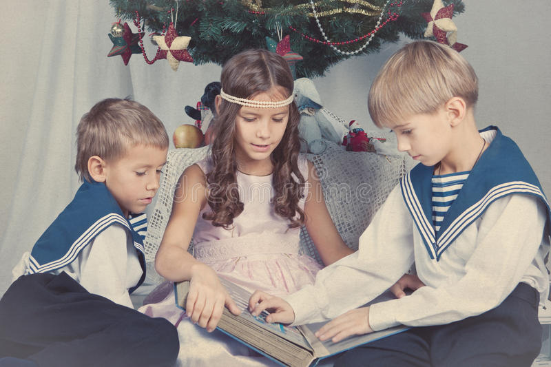 Drei Kinder sitzen um den Weihnachtsbaum lizenzfreies stockfoto