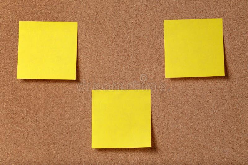 Drei klebrige Anmerkungen der Anzeige über Korkenbrett stockbild