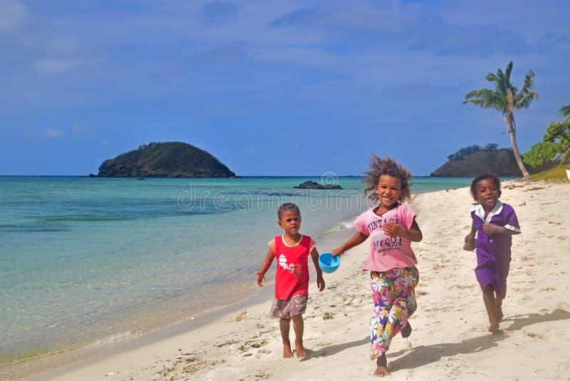 Drei kleine Fijiankinder von Yasawa-Inseln, die in Richtung zur Kamera laufen lizenzfreie stockfotos