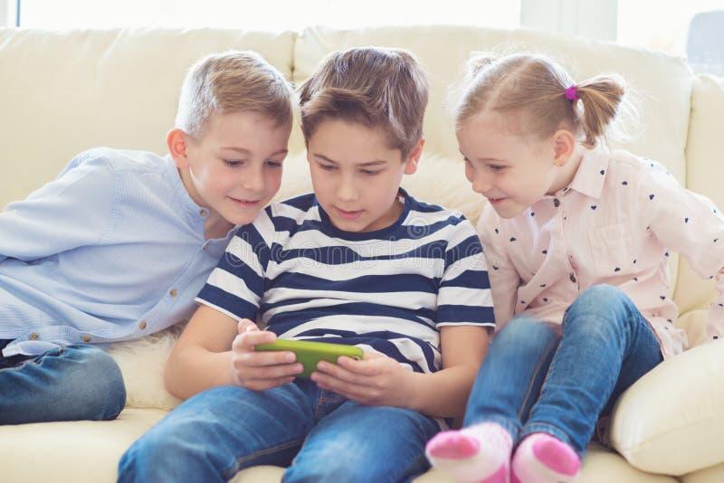 Drei kleine Kinder, die mit Tabletten-PC spielen lizenzfreie stockbilder