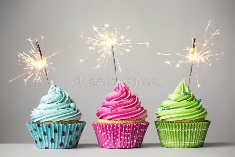 Drei kleine Kuchen mit Wunderkerzen lizenzfreies stockfoto