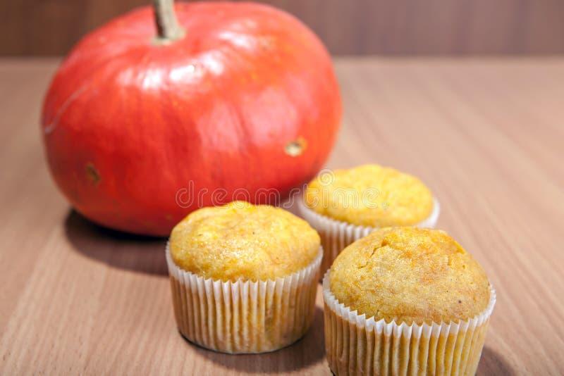 Drei kleine Kuchen und Kürbis auf hölzerner Beschaffenheitstabelle lizenzfreie stockfotos
