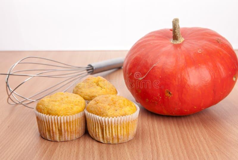 Drei kleine Kuchen und Kürbis auf hölzerner Beschaffenheitstabelle stockfotos
