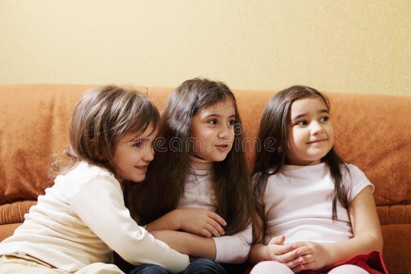Drei kleine Mädchen auf Sofa lizenzfreies stockbild