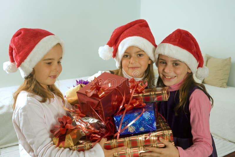 Drei kleine Mädchen mit Weihnachtsgeschenken lizenzfreie stockfotos