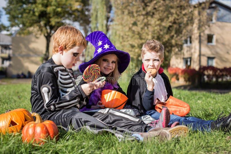 Drei kleine nette Freunde, die auf dem Gras sitzen und Halloween-Süßigkeiten essen stockbild