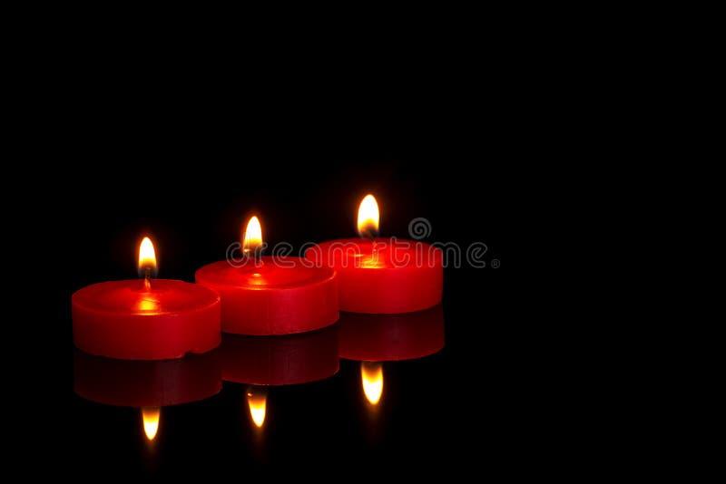 Drei kleine rote Kerzen, tealights, brennend nachts auf Schwarzem In memoriam oder religiös möglicherweise lizenzfreies stockfoto