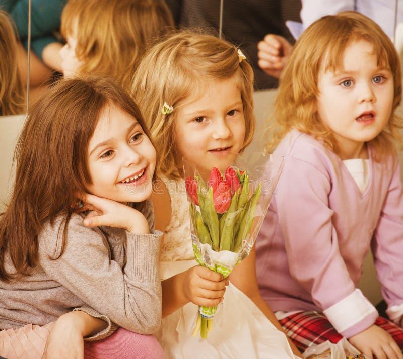 Drei kleine verschiedene Mädchen an der Geburtstagsfeier lizenzfreie stockbilder