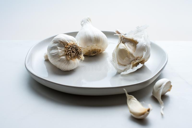 Drei Knoblauchknollen auf einer weißen Platte stockfotografie