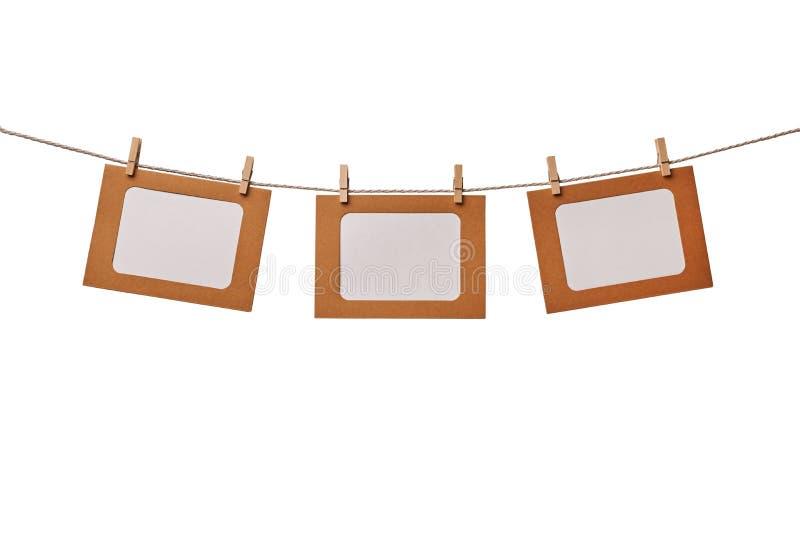 Drei Kraftpapierfotorahmen, die am Seil lokalisiert auf weißem Hintergrund hängen lizenzfreie stockbilder