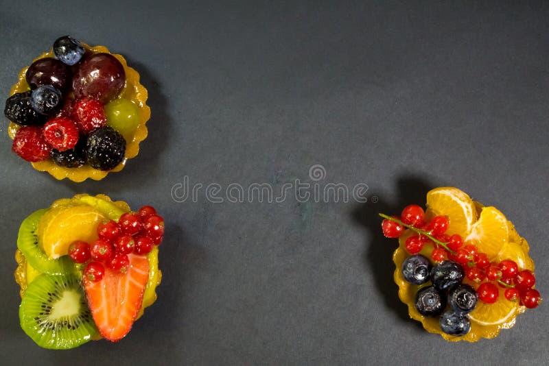 Drei Kuchen mit frischen Biofrüchten, Orange, Kiwi, Erdbeeren, Blaubeeren, rote Johannisbeeren, Trauben, Himbeeren, Brombeeren, F stockfotografie