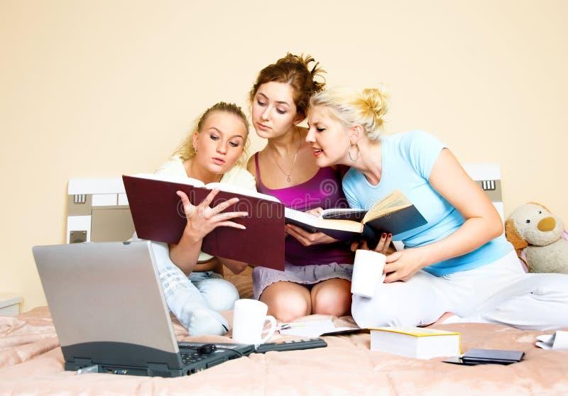 Drei Kursteilnehmer, die ein Buch lesen stockbild