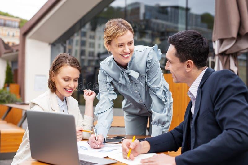 Drei lächelnde Führer, die produktive Teamwork genießen stockbild