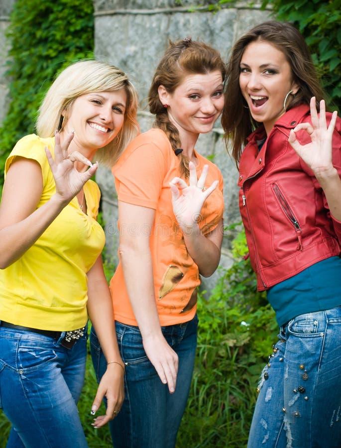 Drei lächelnde Frauen, die okey zeigen lizenzfreies stockbild