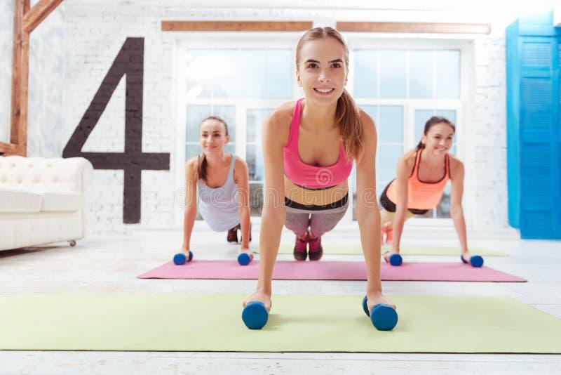 Drei lächelnde Frauen, die zusammen in der Planke stehen stockbilder