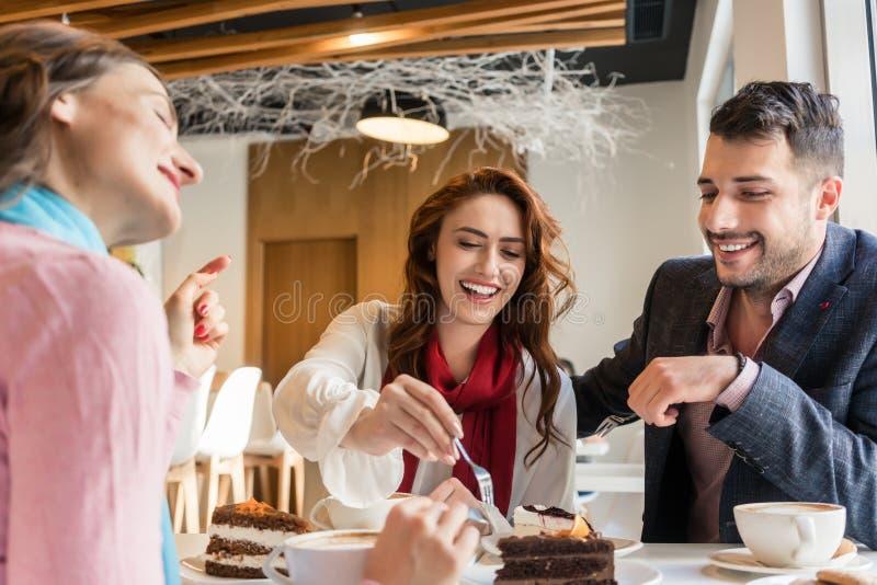 Drei lächelnde Freunde beim Essen von köstlichen Kuchen an ihrem Betrügertag stockfotografie