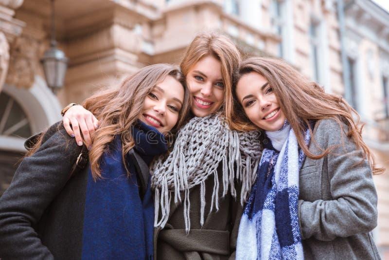 Drei lächelnde Freundinnen, die zusammen stehen lizenzfreie stockfotografie