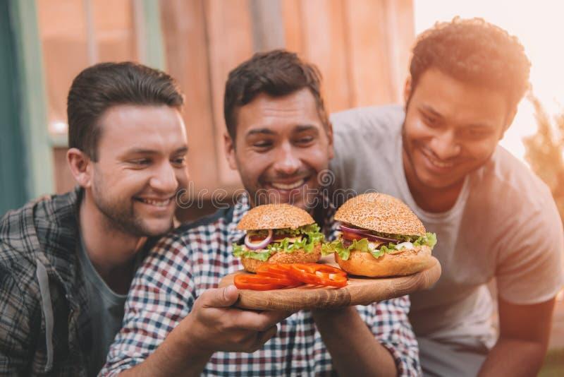 Drei lächelnde Männer, die frische selbst gemachte Hamburger betrachten lizenzfreie stockfotografie
