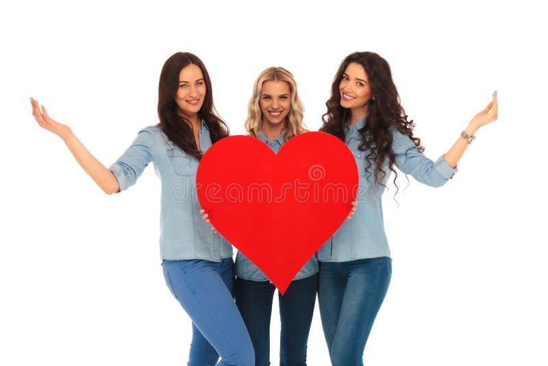 Drei lächelnde zufällige Frauen, die zu ihrem Herzen begrüßen lizenzfreies stockbild