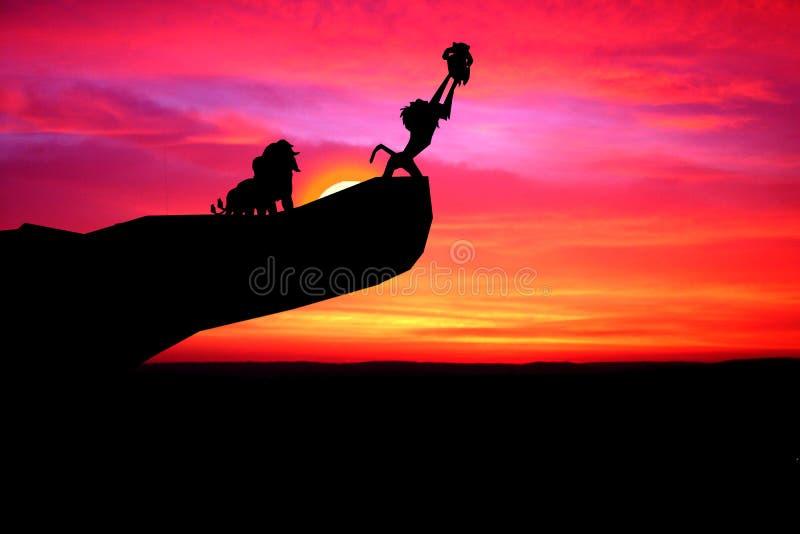 Drei Löwen und ein Affe beobachten den Sonnenuntergang auf einer Klippe Der Affe hält den kleinen Löwen wie der Film Lion King stockfotos