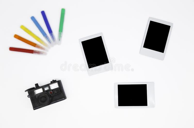 ` Drei leere sofortige Fotorahmen mit einer Minikamera und bunten einem Markierungen ` lizenzfreie stockbilder