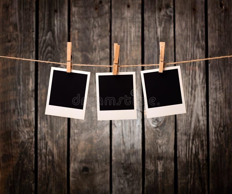 Drei leere sofortige Fotos auf der Wäscheleine stockbild