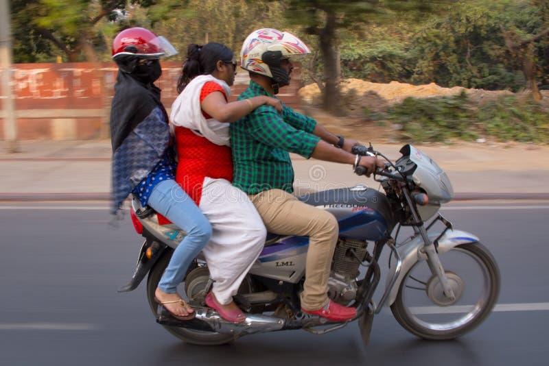 Drei Leute auf einem motocycle, das in die Straße, Neu-Delhi, herein fährt stockfoto