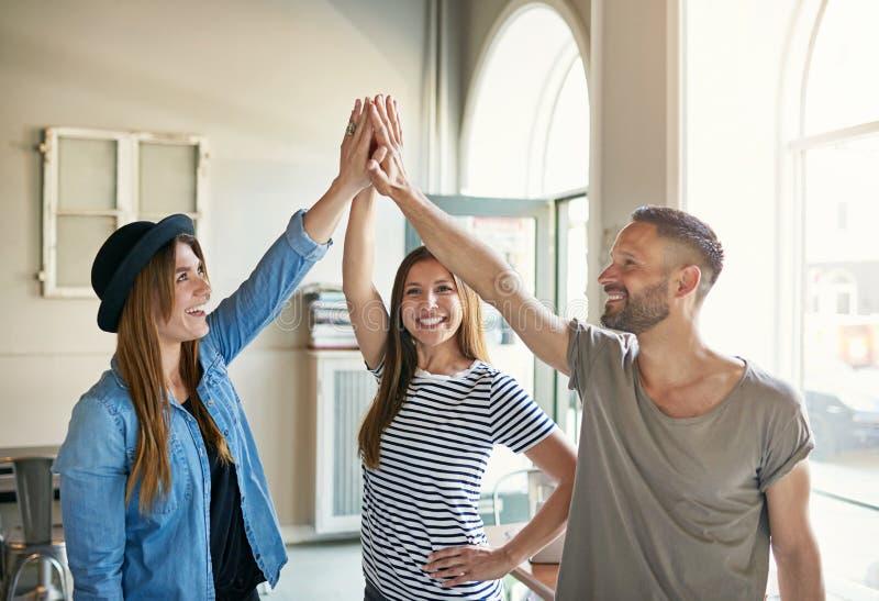 Drei Leute, die Hoch fünf stehen und geben lizenzfreie stockbilder