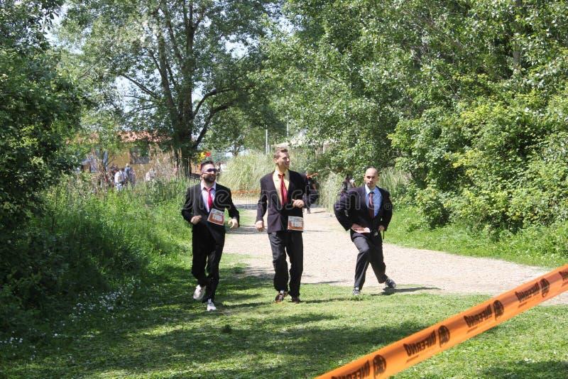 Drei Leute, die in ihre Anzüge laufen lizenzfreie stockfotografie