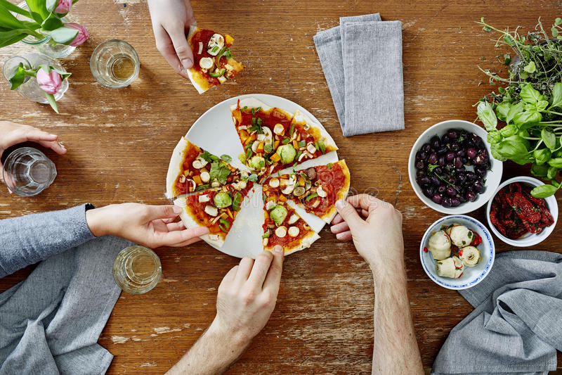 Drei Leute, die organische köstliche Pizza am Abendessen teilen lizenzfreie stockfotografie