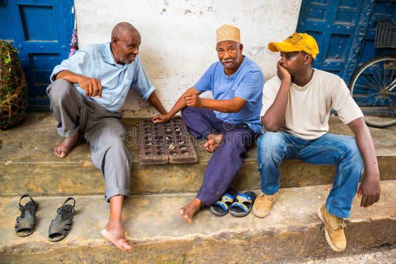 Drei lokale Männer spielen traditionelles Brettspiel Mancala Steinstadt, alte Kolonialmitte von Sansibar-Stadt, Unguja, Tansania stockbild