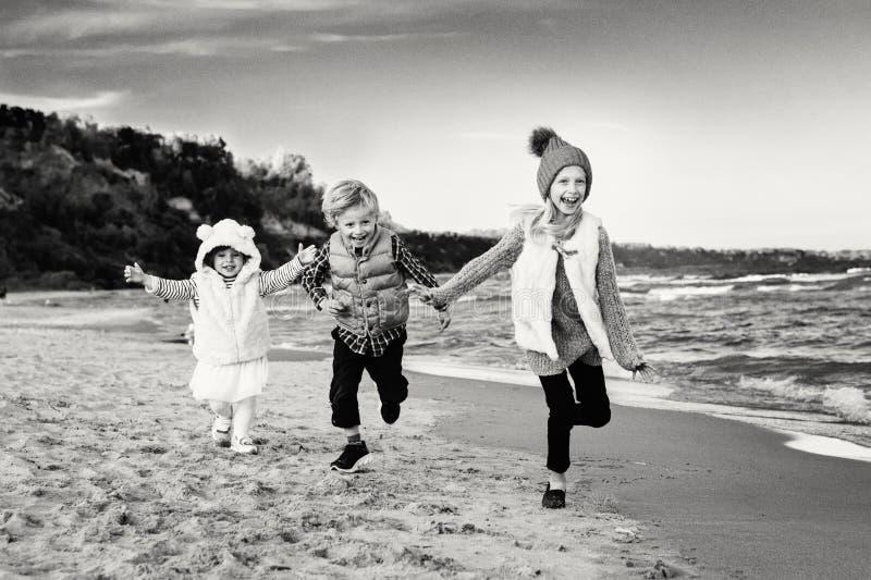 Drei lustige lächelnde lachende kaukasische Kinder scherzt die Freunde, die das Laufen auf Ozeanseestrand spielen stockfotografie