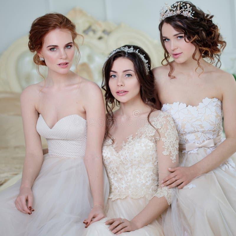 Drei Mädchen in den Brautkleidern Schöne empfindliche Mädchen im Brautsalon stockbild