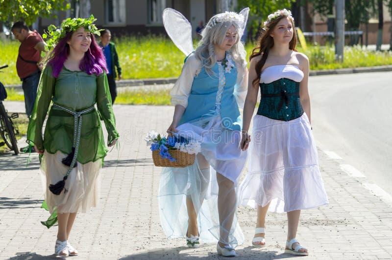 Drei Mädchen in den Feenkostümen, Trickzeichner an einer Kinderparty gehen entlang die Straße in der Stadt, stockbilder