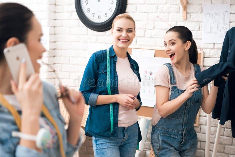 Drei Mädchen an der Kleiderfabrik, die neue Anzugsjacke mit einem von ihnen sprechend am Telefon desining ist lizenzfreies stockbild