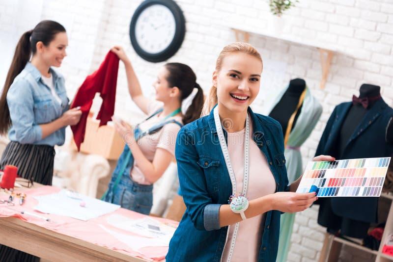 Drei Mädchen an der Kleiderfabrik Eins von ihnen wirft auf Vordergrund mit Farbmuster auf lizenzfreies stockfoto