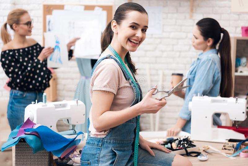 Drei Mädchen an der Kleiderfabrik Sie besprechen Design für neues Kleid Eins von ihnen hält Scheren lizenzfreie stockfotos