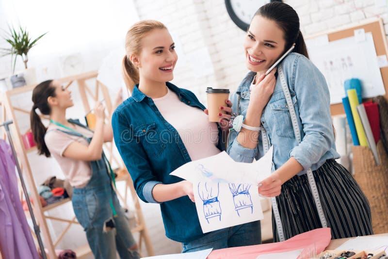Drei Mädchen an der Kleiderfabrik Sie betrachten Pläne und trinkenden Kaffee stockfotografie