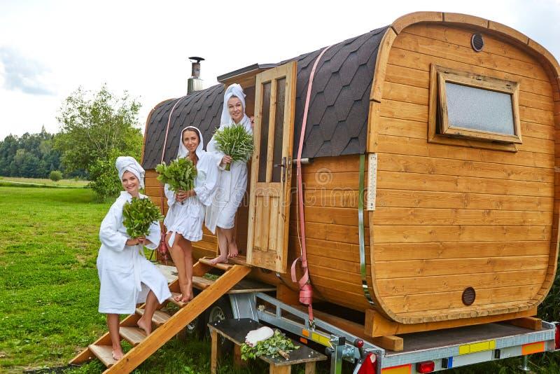 Drei Mädchen, die außerhalb der Sauna sich entspannen lizenzfreies stockbild
