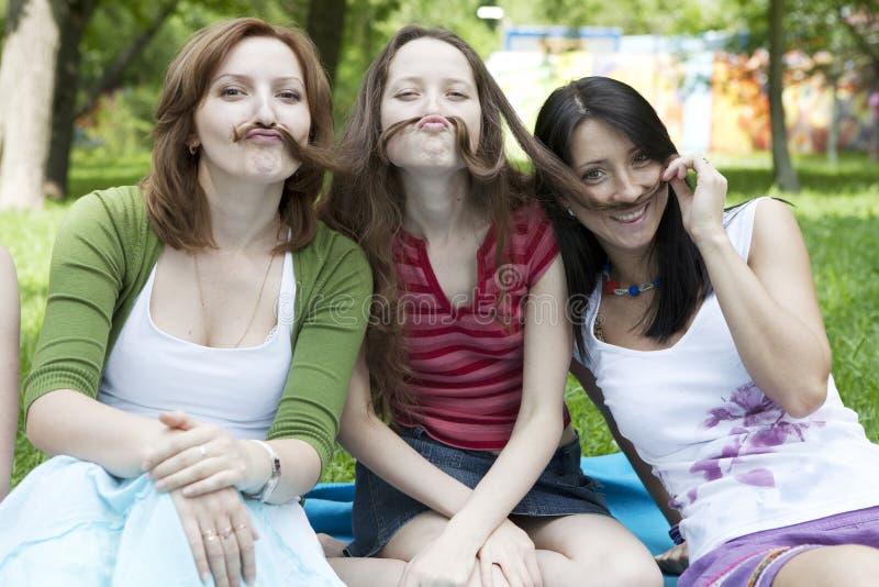 Drei Mädchen, die am Baum sitzen lizenzfreie stockfotos