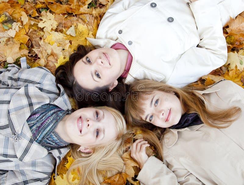 Drei Mädchen, die in den Blättern liegen stockbilder
