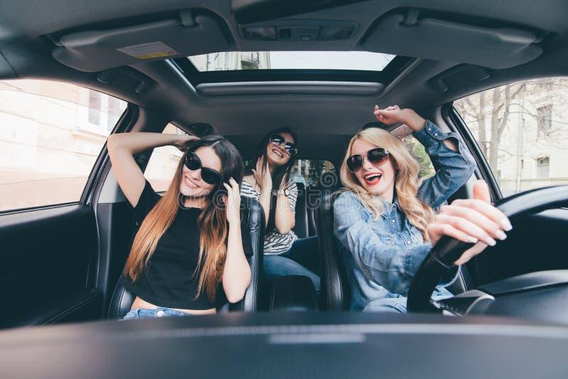 Drei Mädchen, die in ein konvertierbares Auto fahren und Spaß haben, hören Musik und tanzen stockfotos