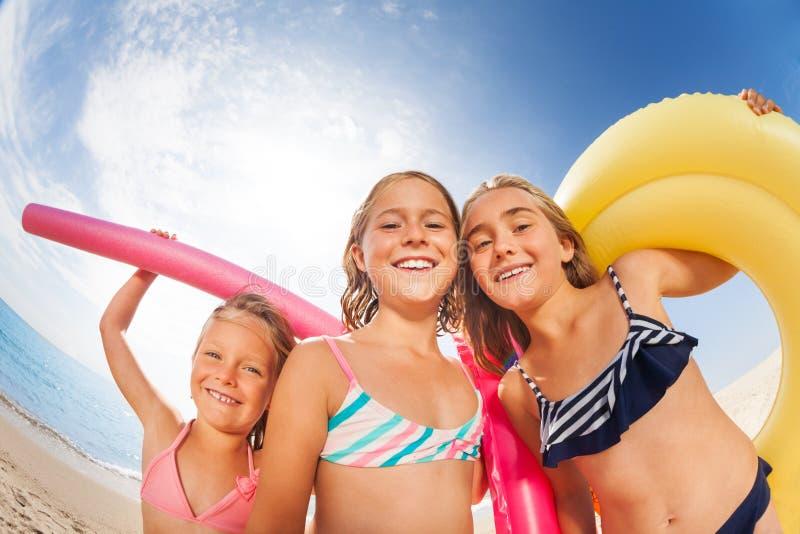 Drei Mädchen, die Spaß auf dem Strand in der Sommerzeit haben stockfotos