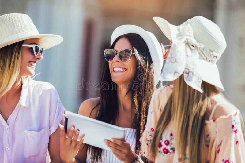 Drei Mädchen mit bunten Einkaufstaschen unter Verwendung der digitalen Tablette stockbilder