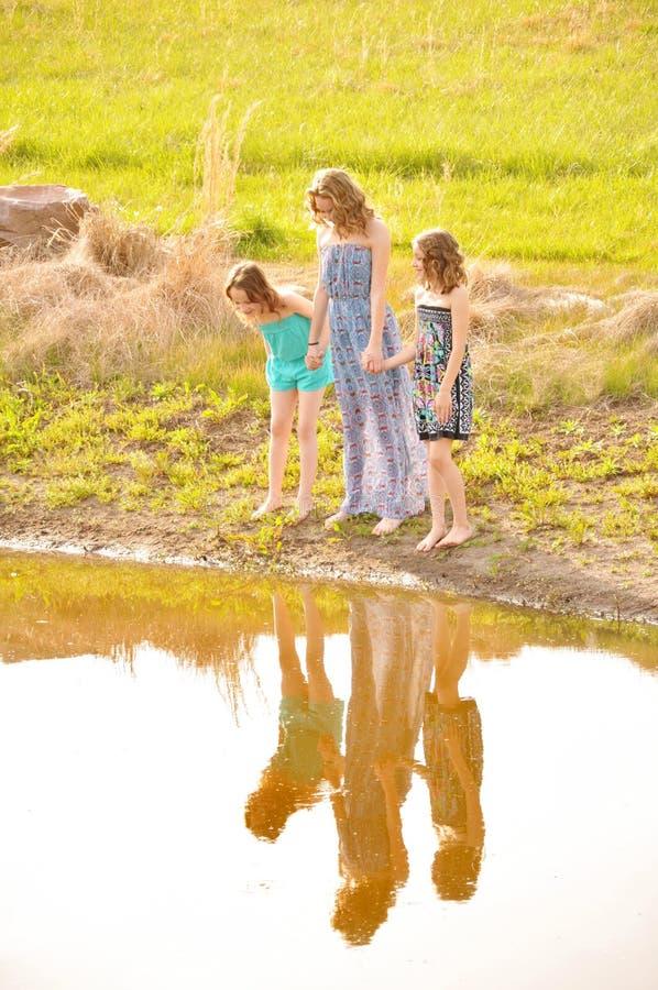 Drei Mädchengriffhandwasserreflexion stockbilder