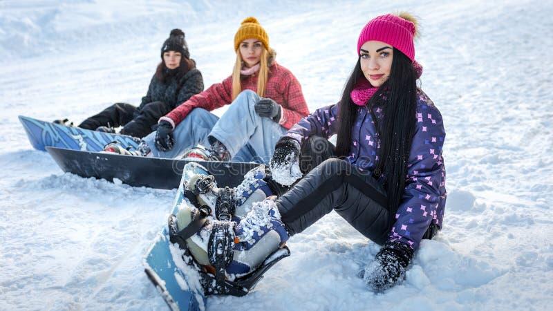 Drei Mädchensnowboarder, die auf dem Schnee sitzen stockfotografie