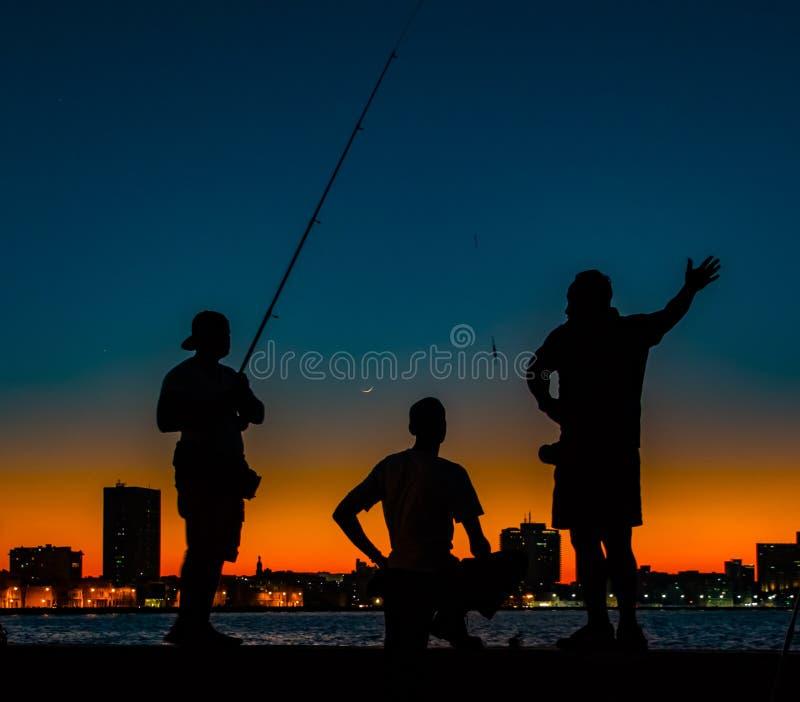 Drei Männer gesehen im Schattenbild, fischend von einem Pier bei Sonnenuntergang lizenzfreie stockbilder